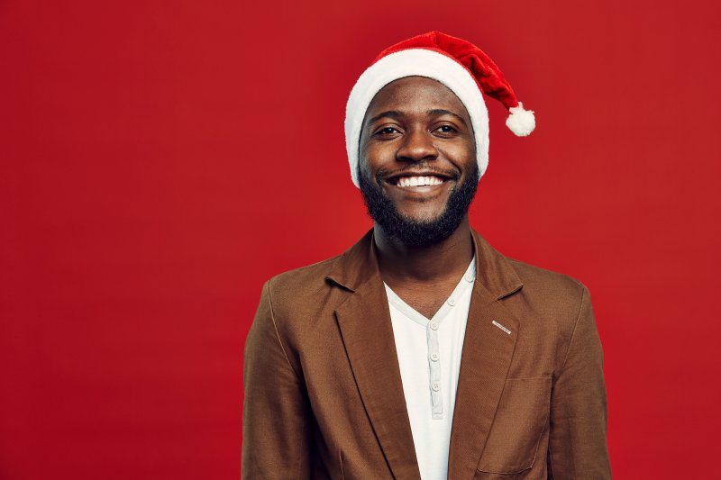 a man wearing a Santa hat and smiling