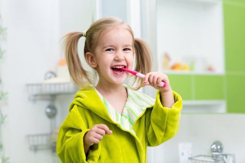 young girl smiling brushing teeth